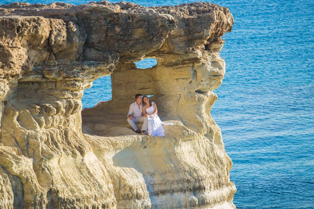 חתן וכלה מצטלמים על צוק בקפריסין
